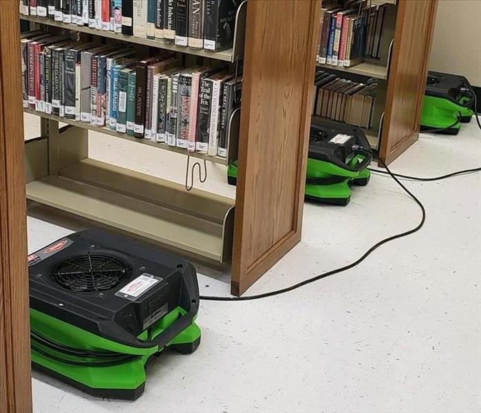 SERVPRO fans sitting between shelves of books at the library.