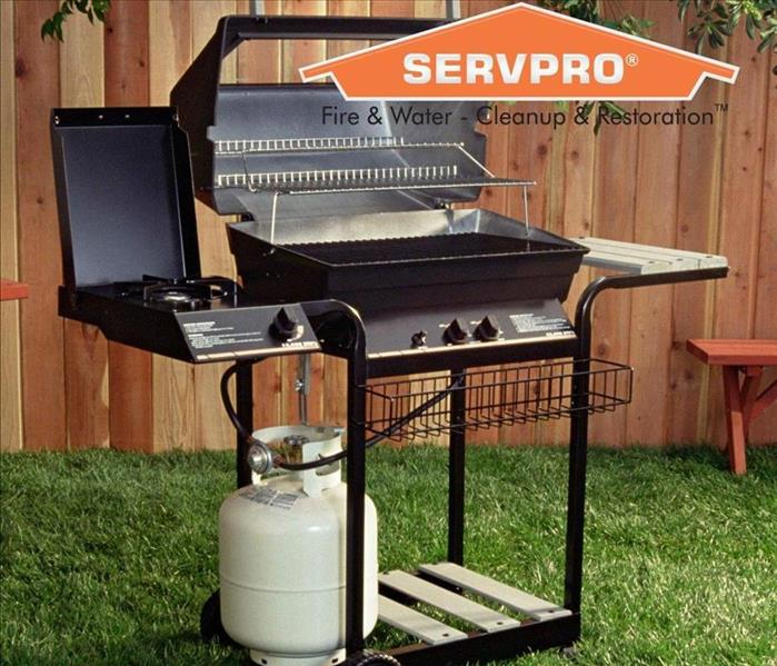 Agas grill sitting in a yard with the SERVPRO logo.