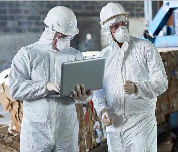 SERVPRO employees with personal protective equipment with a laptop.