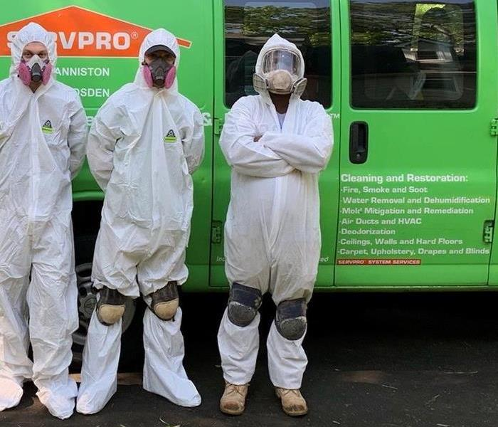 Three crew members in Tyvek suits in front of a green SERVPRO van.