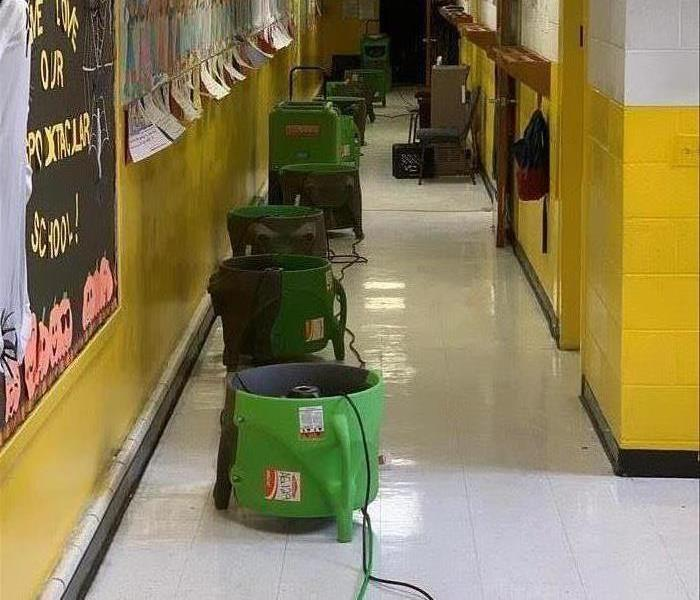 SERVPRO air movers lined down a hallway.